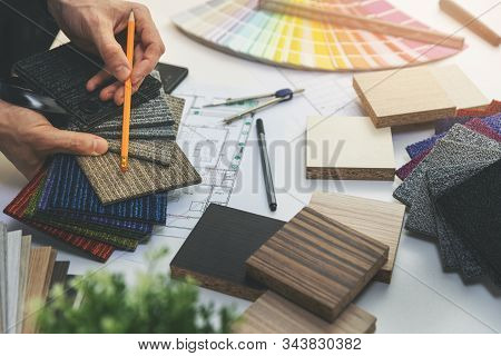 Designer Choosing Flooring And Furniture Materials From Samples For Home Interior Design Project