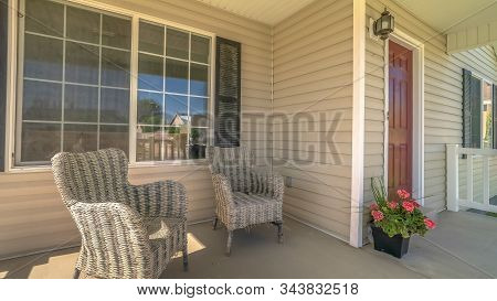 Pano Frame Wicker Armchairs On The Sunlit Front Porch Of Home With Brown Front Door