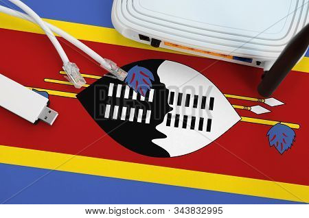 Swaziland Flag Depicted On Table With Internet Rj45 Cable, Wireless Usb Wifi Adapter And Router. Int