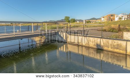 Pano Bridge Over Lake With Lakefront Buildings And Mountain View Under Blue Sky