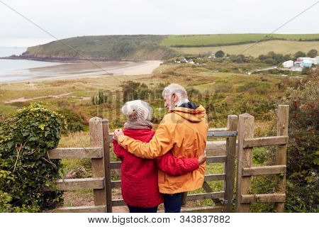Rear View Of Active Senior Couple Looking Out Over Gate As They Walk Along Coastal Path In Fall