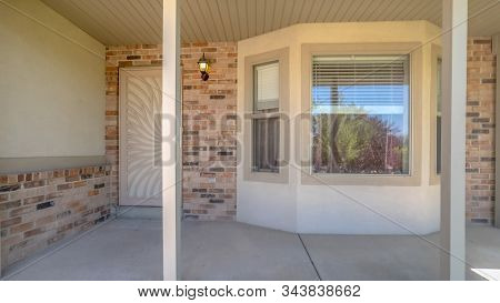Pano Home Facade With Bay Window And Front Porch Supported By White Pillars