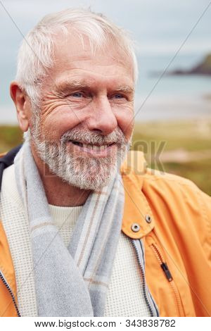 Active Senior Man Walking Along Coastal Path In Fall Or Winter By Gate With Beach And Cliffs Behind