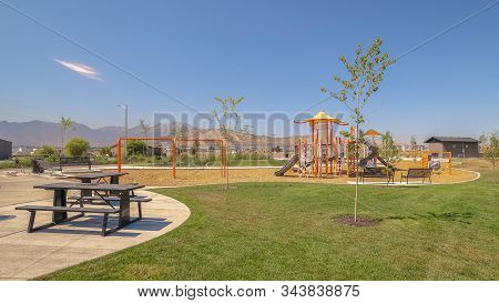 Pano Scenic Park With Picnic Tables And Benches And Playground Against Blue Sky