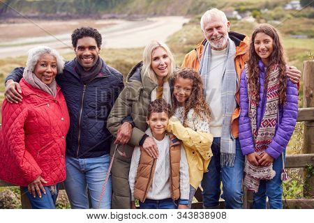 Portrait Of Active Multi-Generation Family On Winter Beach Vacation Resting By Gate