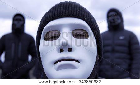 Men In Black Jackets And Masks. Footage. Criminal Gang In Black Plastic Masks And Leader In White Ma