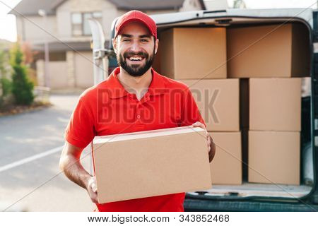 Image of smiling young delivery man in red uniform standing with parcel box near car outdoors