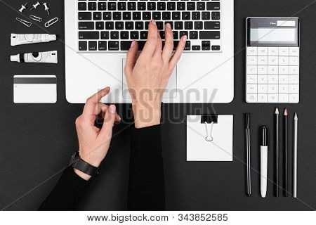 A Man Works With Laptop, Laptop, Calculator, Pens, Pencils, Card, Phone On His Desktop Isolated On B