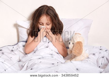 Image Of Sneezing Sick Little Girl With Fair Hair, Covering Mouth With Napkin, Blowing Nose, Feeling