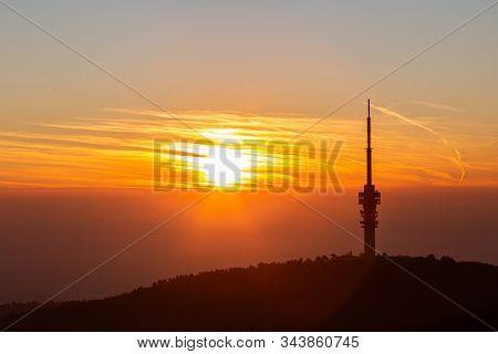 MECSEK HILLS, HUNGARY - JANUARY 2020: TV tower in Pécs city. Beautiful sunrise over hill. Mecsek hills, Hungary.