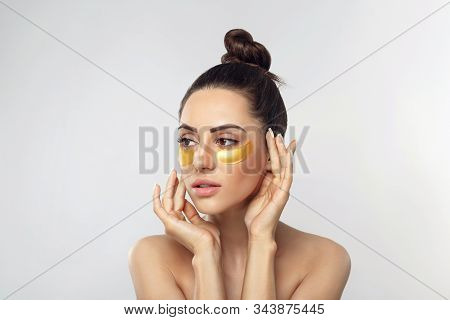 Beautiful Woman With Gold Patches For Eyes On A Grey Background. Patch Under Eyes. Collagen Mask. Po