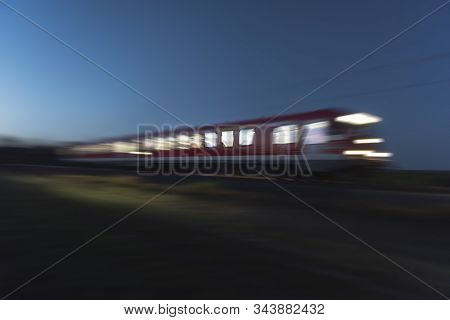 Red Train In Motion With Light At Windows, In The Evening. Traveling By Night. Train Travel. Blur Mo