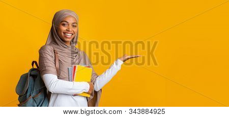 Cheerful Black Islamic Female Student In Hijab Pointing Aside At Copy Space On Yellow Background Wit