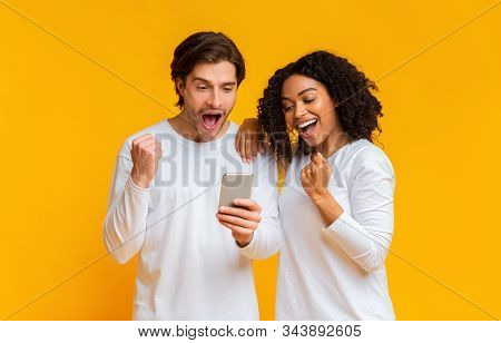 Great News. Happy Interracial Couple Looking At Smartphone Screen And Celebrating Success, Raising H