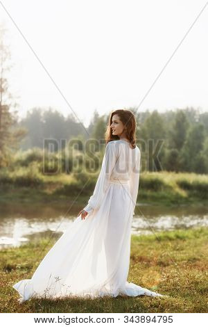 Beautiful Slender Woman In A Long White Dress Walks In The Morning Near The Lake. Brown-haired Girl