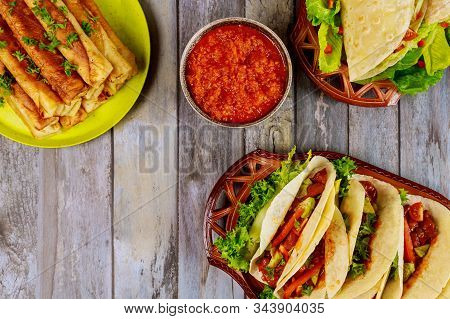 Taquitos, Soft Tortillas And Mild Salsa On Wooden Table.
