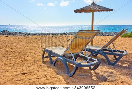 Sandy beach with parasol and chaise longues by the sea on sunny summer day