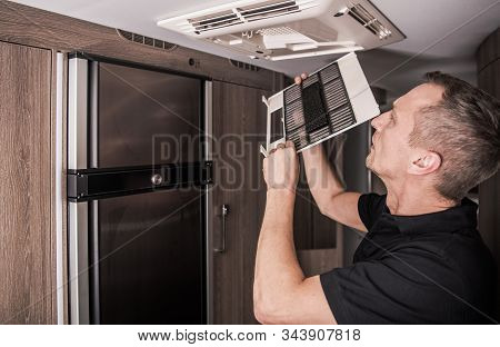 Rv Recreational Vehicle Air Condition Filter Cleaning By Caucasian Men In His 40s.
