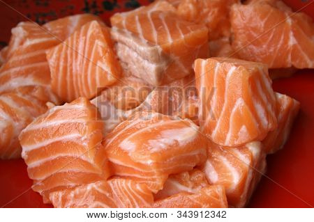 Pieces Of Red Salmon Fish On A Red Plate. Slices Of Fresh Fish Fillet On A Dish.