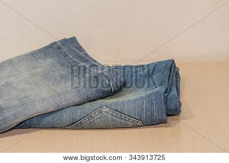 Two Pairs Of Denim Jeans Folded Neatly On Wood Grain Table Top.