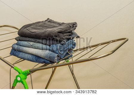 Closeup Of Four Pairs Of Denim Jeans Folded And Stacked Neatly On Fordable Drying Rack.