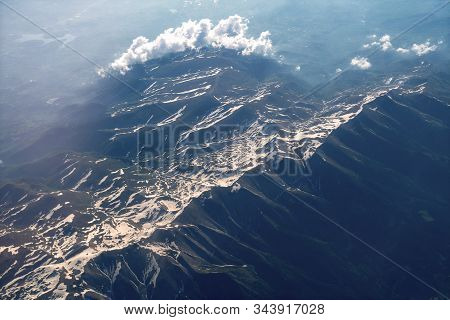 Top View On Mountains During Sunrise. Mountain Peak Of Rocks Covered By Clouds And Fog. Aerial View