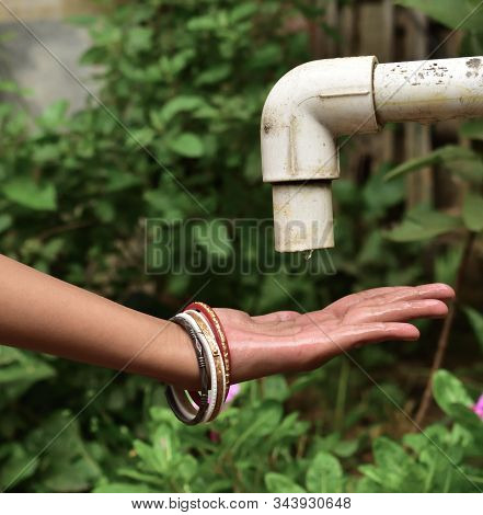 Water Drop Pours From The Old Crane Into The Hands. The Concept Of Water Scarcity.