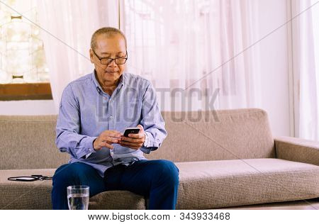 Senior Asian Man Wearing Glasses And Using Mobile Phone At Home,relax Time,senior Lifestyle Concept,