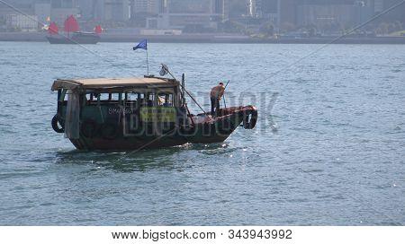 Hong Kong, East Asia - November 22, 2019: Man Fishing From Chinese Fishing Junk In Aberdeen Harbor,