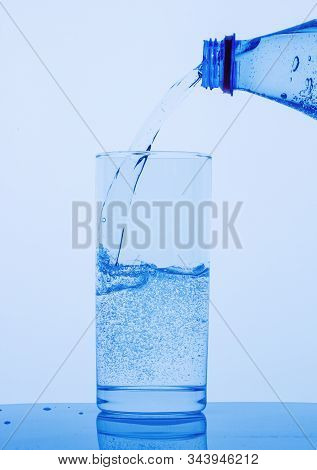 Crystal Clear Drinking Mineral Water From A Bottle Is Poured Into A Glass