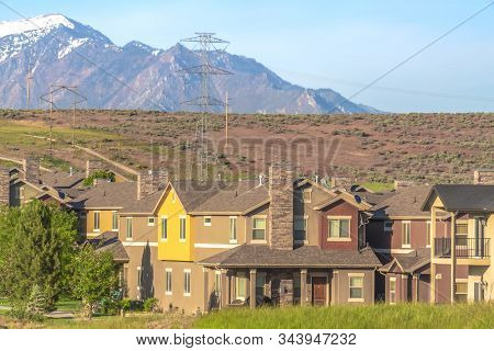 Exterior Of Homes In The Suburb With Power Lines Mountain And Sky Background