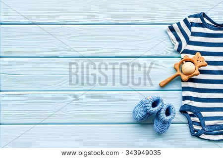 Newborn Baby Boy Set - Blue Clothes As Bodysuit, Booties, Toys - On Blue Wooden Table Top-down Frame