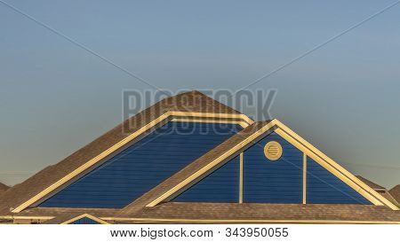 Panorama Close Up Of Roof Structure Of Home With Blue Gable Wall And Round Gable Window
