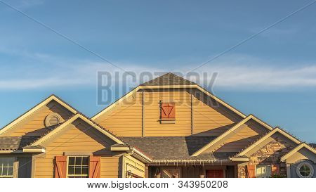 Panorama House Exterior With View Of The Gable Roof With Gable Windows Against Blue Sky