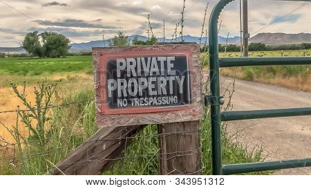 Panorama No Trespassing Sign On The Wire Fence And Green Metal Gate Of Private Property