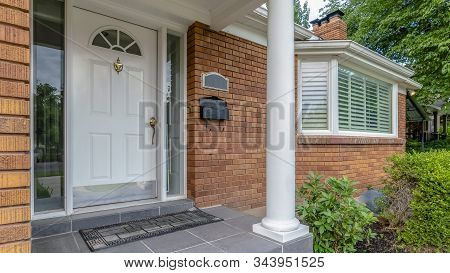 Panorama Facade Of Home With Brick Exterior Wall Porch Bay Windows And White Front Door