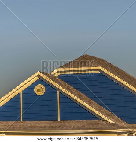 Square Frame Close Up Of Roof Structure Of Home With Blue Gable Wall And Round Gable Window