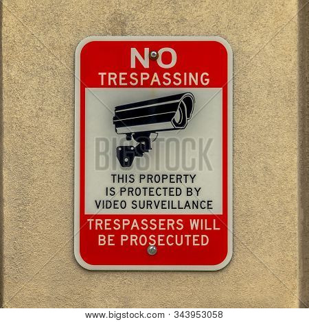 Square Building Exterior With Close Up View Of No Trespassing Sign On Concrete Wall