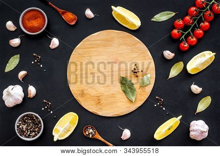 Mockup For Menu. Cutting Board Near Spices And Vegetables On Black Background Top-down