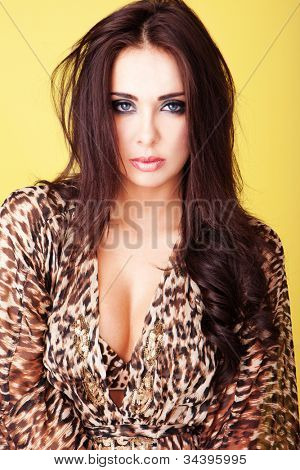 Beautiful busty brunette woman in an animal print blouse with plunging neckline showing her cleavage
