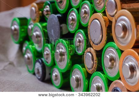 Old Used Batteries Are Stacked. Close-up Of Oxidized Rotten Aaa And Aa Size Batteries. Recycling Old