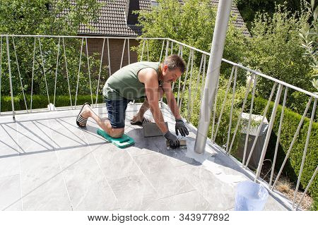 Tiler Laying  Tiles On The Floor Of A Balcony And Grouted.