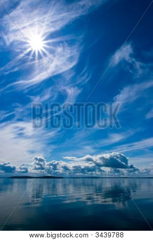 Rays Of Sun On Blue Sky Reflecting In Lake