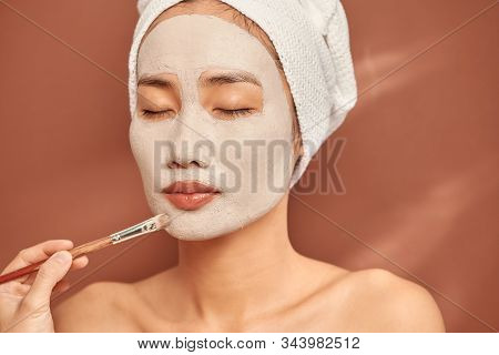 Spa Asian Girl Applying Facial Clay Mask. Beauty Treatments. Over Blue Background.