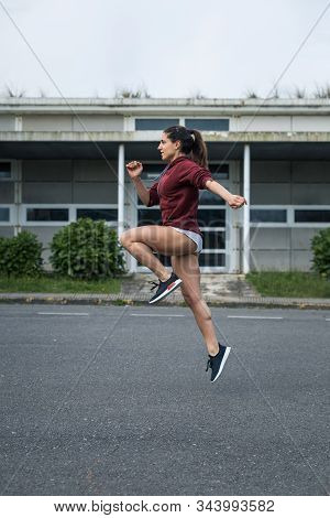 Female Athlete Running And Jumping. Sporty Young Woman Soing Technique Exercise On Asphalt.