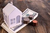 Mortgage or home ownership investment concept. Money and white toy house on table. US dollars and coins. Saving money for private house. Estate investment. Copy space. Close-up. poster
