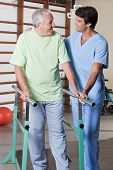 Senior man having ambulatory therapy with his therapist. poster