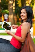 Pretty girl outdoors sitting and showing on her touchcreen tablet. poster