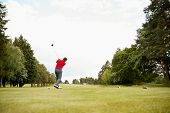 Mature Male Golfer Hitting Tee Shot Along Fairway With Driver poster