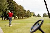 Mature Male Golfer Hitting Tee Shot Along Fairway With Driver Viewed Through Buggy Window poster